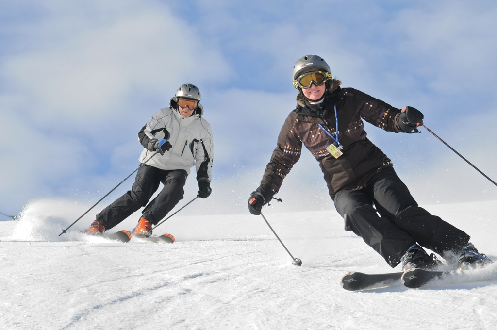 Two people downhill skiing